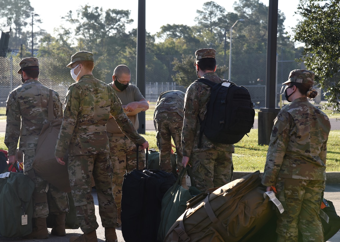 Members of the Air National Guard and the 403rd Wing work together loading bags onto a truck at Camp Gulfport, which is located at the Gulfport Combat Readiness Training Center, where one Restriction of Movement operation was set up in order to prevent the spread of COVID-19. ROMs were put into effect before all deployments start, in order to ensure the safety of service members in the U.S. Central, Africa, and European Commands area of responsibilty. (U.S. Air Force photo by Jessica L. Kendziorek)