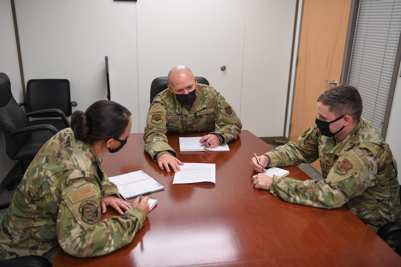 Three Airmen sit around a table to create a force development tool to enhance service member career plans.