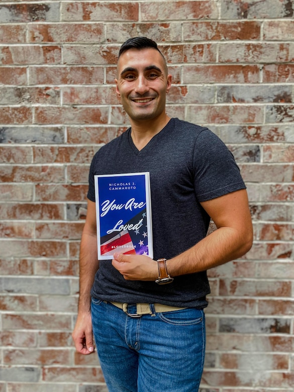 "Air National Guard Senior Airman Nicholas Cammaroto poses with a copy of his recently published, debut book, ""You Are Loved."""