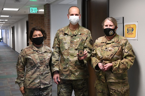Lt. Col. Kimberly MacPherson (right), 34th Aeromedical Evacuation Squadron commander, and Tech. Sgt. Diane Decker, 34 AES medical administration Air Reserve Technician, present Col. Christopher Zidek, 302nd Airlift Wing commander, a squadron patch during his visit with the 34 AES, Dec. 6, 2020, at Peterson-Schriever Garrison, Colorado