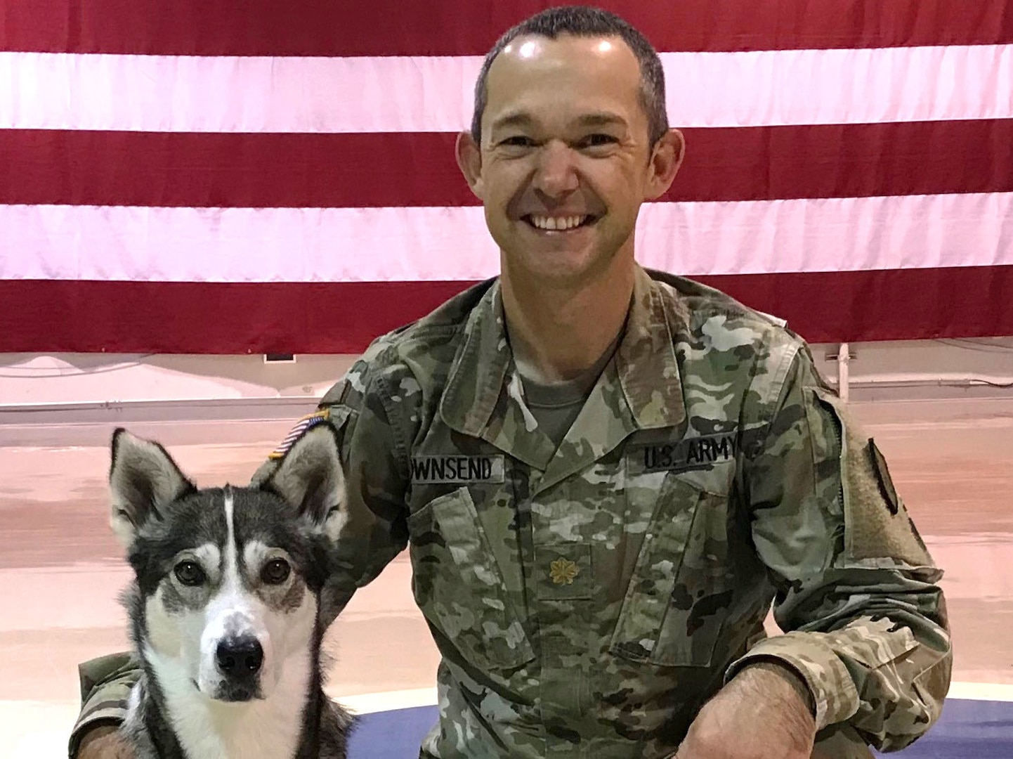 Maj. Troy Townsend, director of behavioral health, office of the state surgeon, New Hampshire Army National Guard, poses with therapy dog Cache Aug. 13, 2019. Cache, a 9-year-old retired sled dog, travels with Townsend across New Hampshire to meet Guard members.