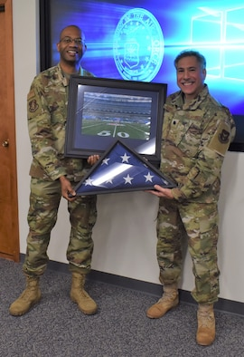 Col. Ricardo Baker, 655th Intelligence, Surveillance, and Reconnaissance Group commander, presents Lt. Col. Thomas Danas, 655th ISR Group deputy commander, a flag and framed photo during his retirement ceremony Dec. 5, 2020. Danas has held multiple positions within the enterprise since 2013 with both the 16 Intelligence Squadron and 655 ISRG and is retiring after more than 41 years of service; over 20 years enlisted and over 20 years as an officer.
