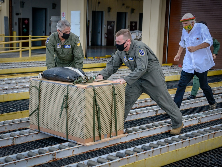 """Brig. Gen. Jeremy Sloane, 36th Wing commander, and Col. Kevin Martin, 374th Operations Group commander, make the ceremonial """"push"""" of the first pallet to kick-off Operation Christmas Drop at Andersen Air Force Base, Guam, Dec. 7, 2020."""