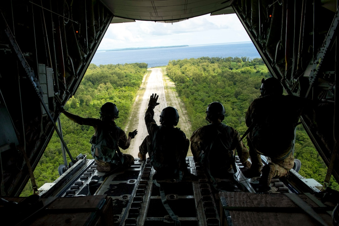 Four airmen, shown from behind in silhouette, wave from the open back of an aircraft flying over an island.