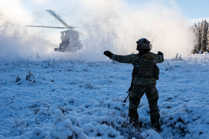 An airman directs a helicopter landing.