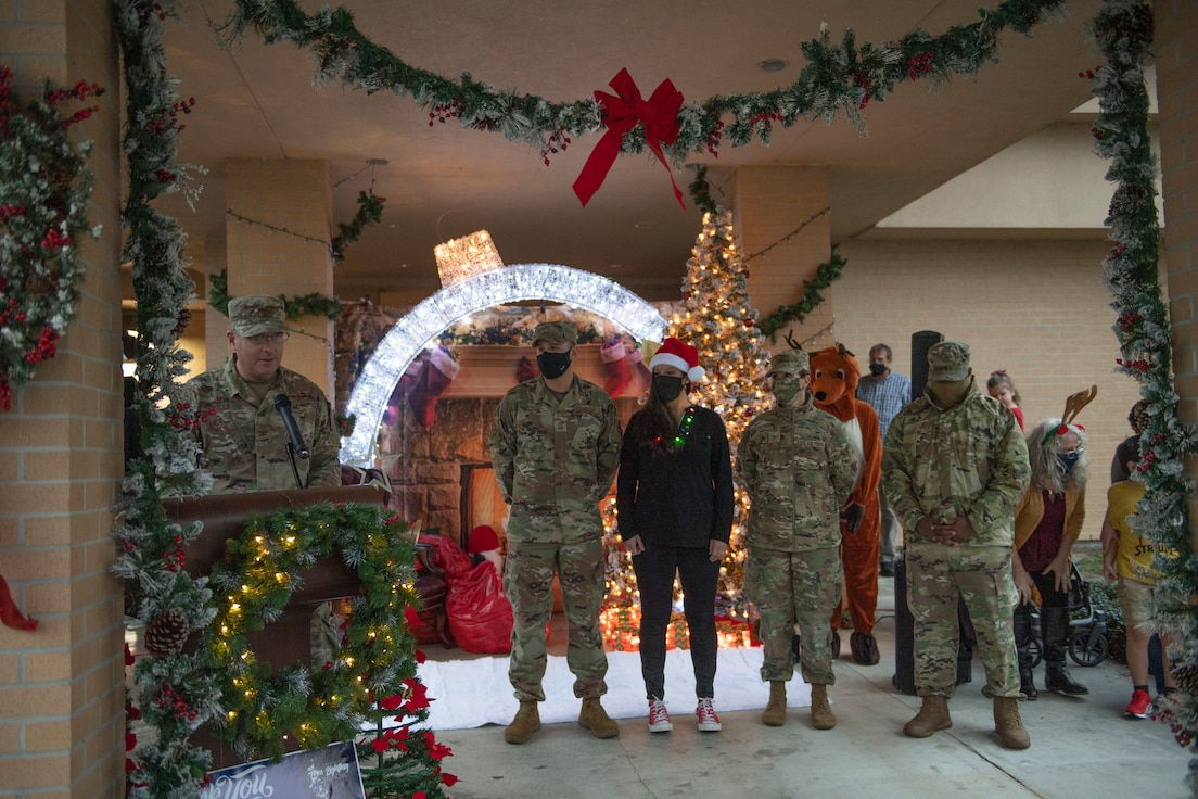 A photo of Airman standing in front of holiday decorations, while Col. Dan Walls speaks at a virtual tree-lighting ceremony.