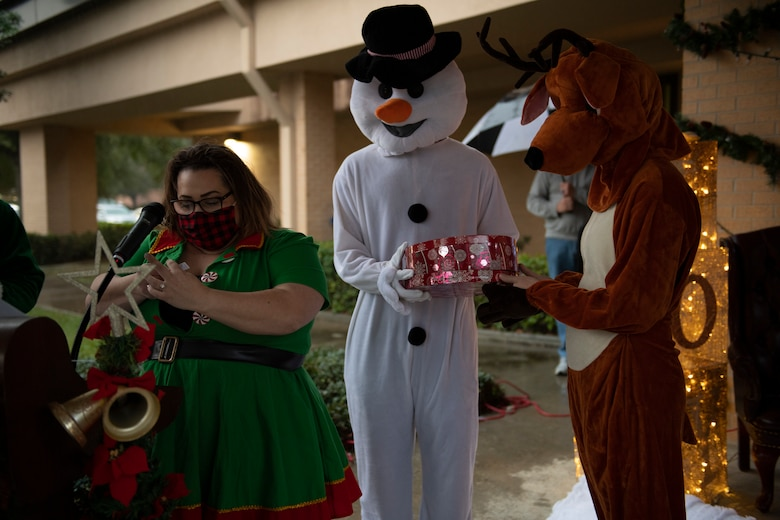 A photo of Sarah Pfau, a snowman costume and a reindeer costume, announcing the winners of a raffle during a virtual tree-lighting ceremony.