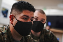 U.S. Marine Corps Gunnery Sgt. Guillermo Garcia, left, and Sgt. Caleb Chase, defensive cyberspace operators with 9th Communication (Comm) Battalion, I Marine Expeditionary Force Information Group, test the vulnerability of opposing teams from their laptop while engaged in the Marine Corps 2020 Cyber Games at Marine Corps Base Camp Pendleton, California, Nov. 19, 2020. 9th Comm participated in the cyber games to enhance their skills and to develop tactics and techniques while competing against other teams across the United States. (U.S. Marine Corps photo by Lance Cpl. Patrick Katz)