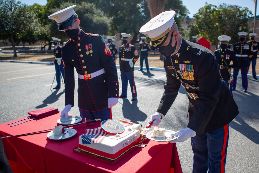 U.S. Marine Corps Cpl. Joshua Matson, left, a data systems administrator with I Marine Expeditionary Force Information Group (I MIG), and Col. Brian Rideout, commanding officer of I MIG, serve cake during a cake cutting ceremony at Marine Corps Base Camp Pendleton, California on Nov. 9, 2020. I MIG hosted the cake cutting ceremony in lieu of the Marine Corps 245th Birthday Ball to honor the long standing tradition of celebrating the birth date and legacy of the United States Marine Corps. (U.S. Marine Corps photo by Cpl. Tia D. Carr)