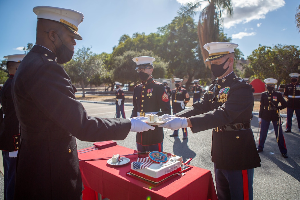 U.S. Marine Corps Maj. Keith Stevenson, left, commanding officer of I Marine Expeditionary Force Information Group (I MIG) Communication Strategy and Operations Company, receives the first slice of cake from Col. Brian Rideout, right, commanding officer of I MIG,  during a cake cutting ceremony at Marine Corps Base Camp Pendleton, California on Nov. 9, 2020. I MIG hosted the cake cutting ceremony in lieu of the Marine Corps 245th Birthday Ball to honor the long standing tradition of celebrating the birth date and legacy of the United States Marine Corps. (U.S. Marine Corps photo by Cpl. Tia D. Carr)