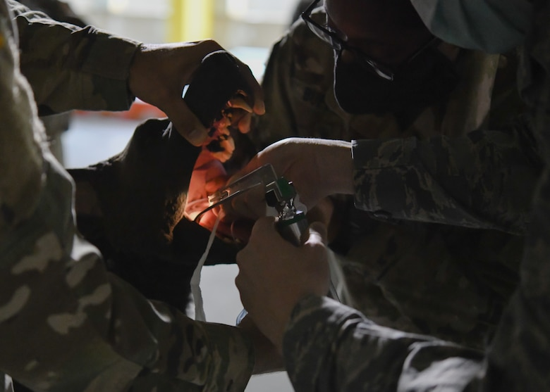 A 316th Medical Group member is guided through a simulated intubation procedure on K-9 Disel, a decoy dog used for training purposes, by U.S. Army Capt. Alexandra Bufford, course instructor and veterinarian at Ft. Belvoir, Va., during a Canine Tactical Combat Casualty Care Course, a training course designed to teach medical professionals how to aid wounded MWDs in deployed conditions, at Malcolm Grow Medical Clinics and Surgery Center at Joint Base Andrews, Md., Nov. 12, 2020.