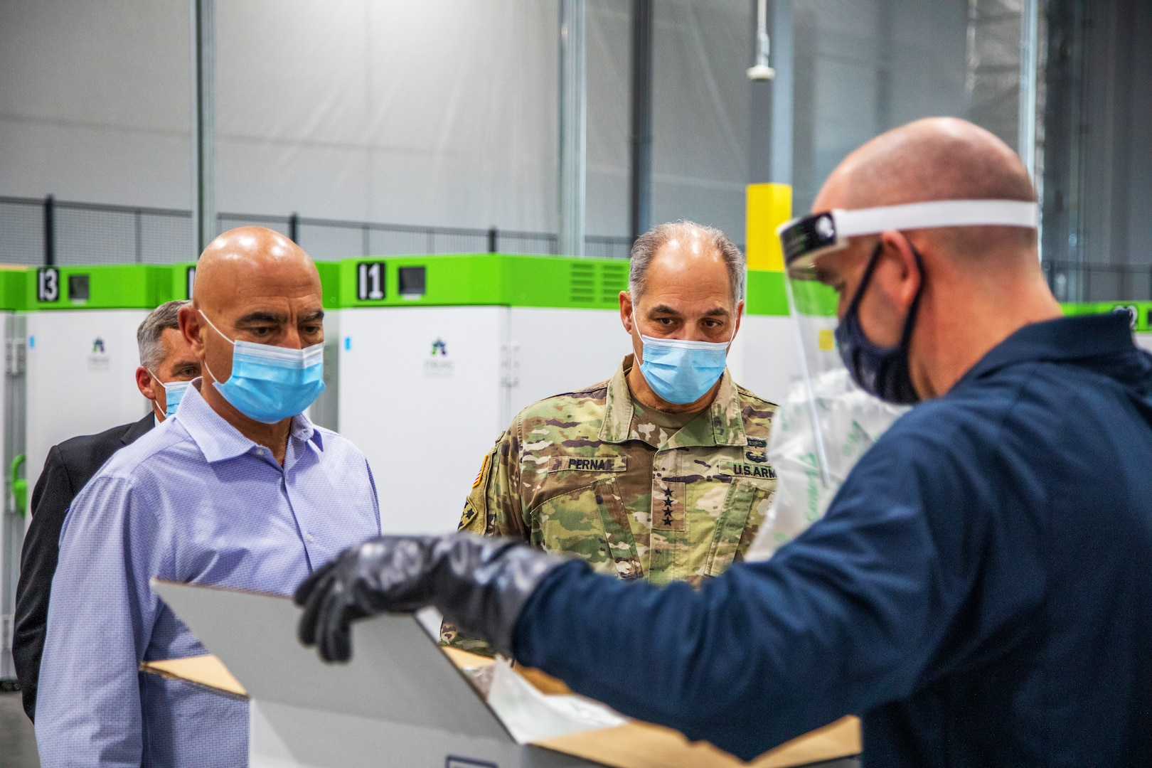A man in a military uniform and two men wearing civilian clothes watch as another man opens a box. All of the men wear face masks.