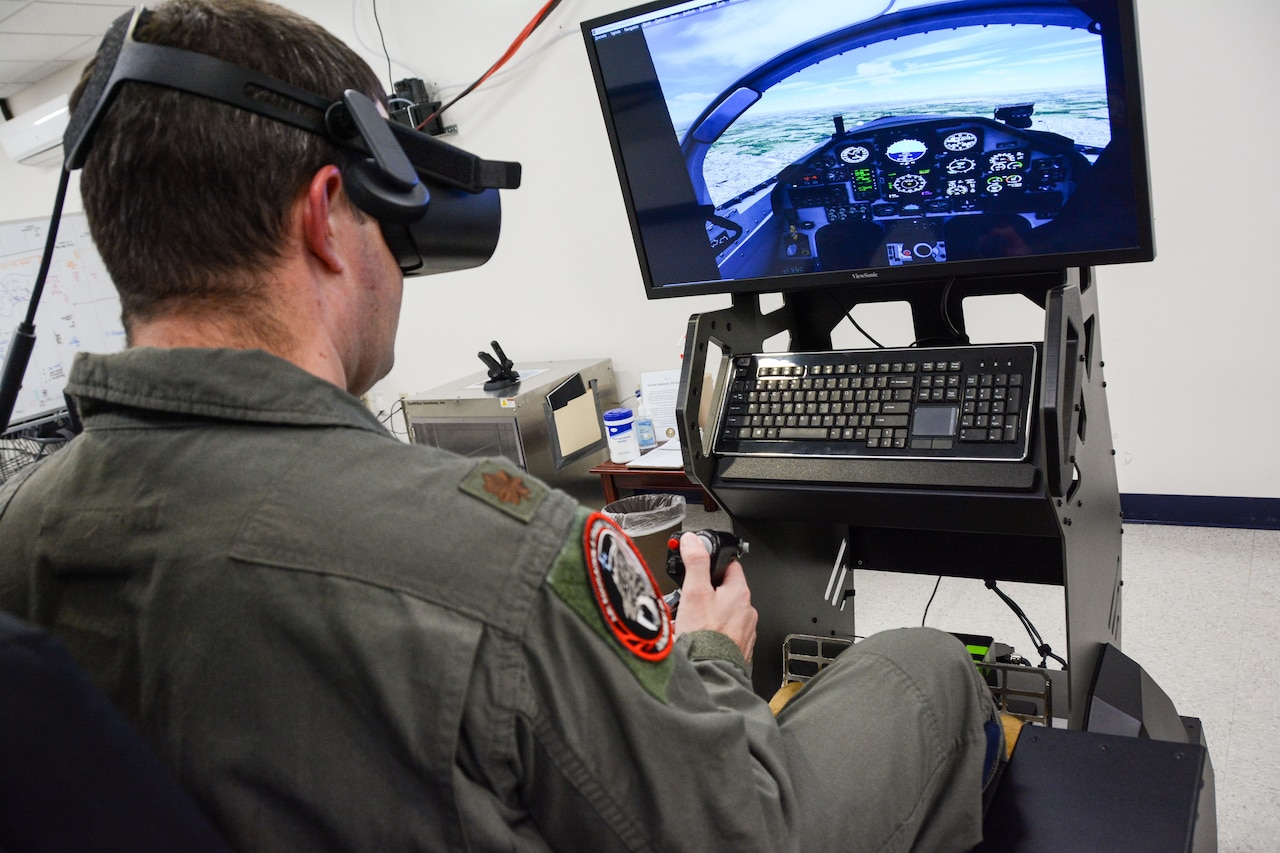 A man in a military flight suit operates an aircraft simulator.