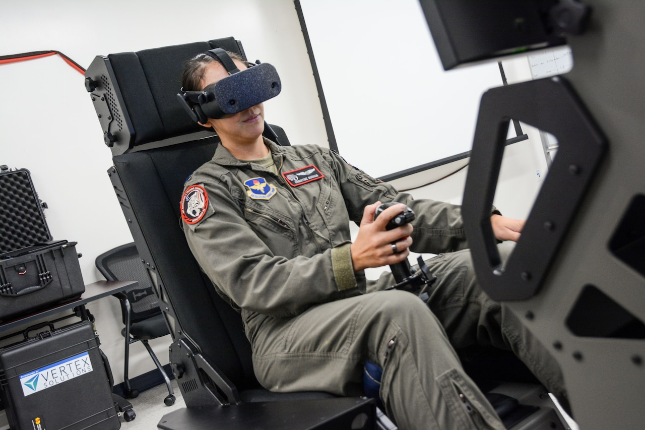 A woman in a military flight suit operates an aircraft simulator.