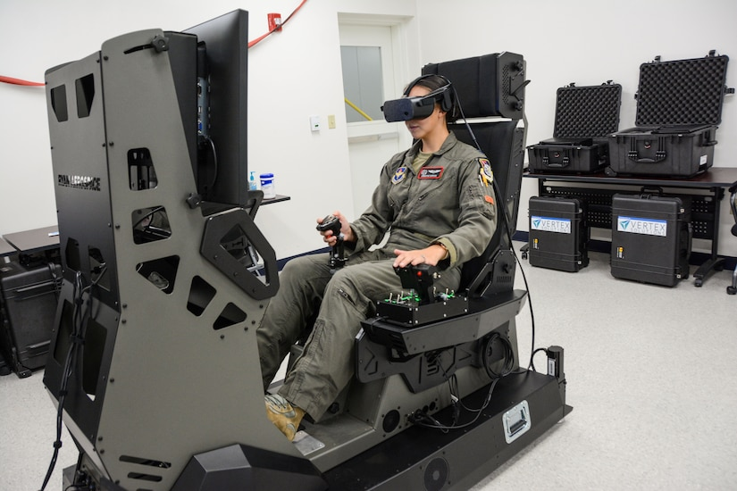 A woman in a military flight suit operates an aircraft simulator. A replica of the  cockpit can be seen on the flight simulator monitor.