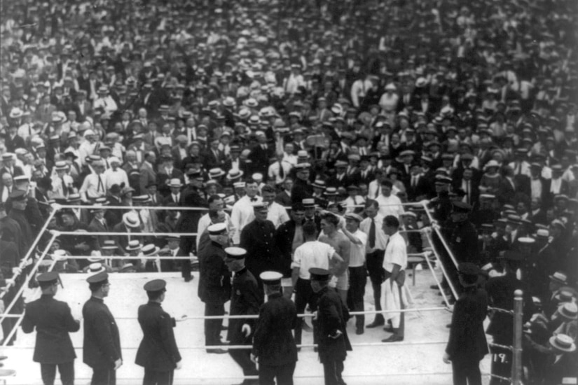 A photo provides an aerial view of a group of people in a boxing ring surrounded by a large crowd.