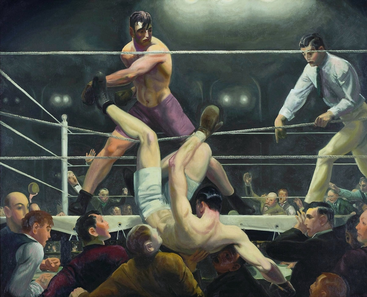 A boxer knocks his opponent from the ring.