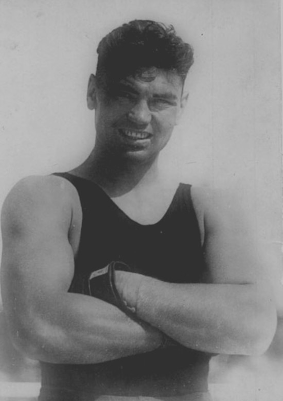 A man wearing a tank top has his arms crossed as he poses for a photo.