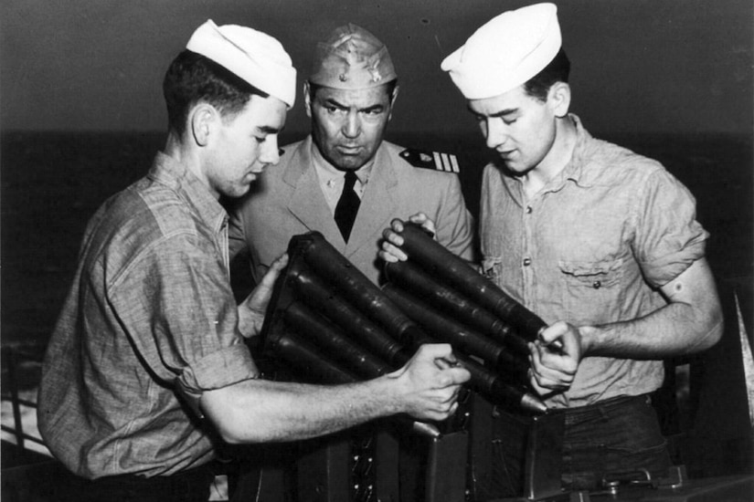 Two young men in sailor uniforms load an antiaircraft gun while an older man in an officer's uniform looks on.