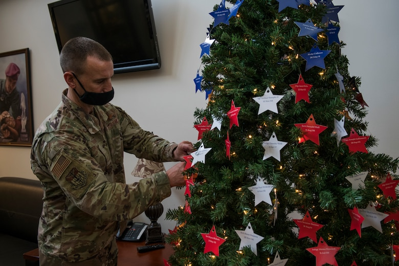 U.S. Air Force Col. Timothy Hood, vice commander of the 1st Special Operations Wing, places stars on an Honor Tree.