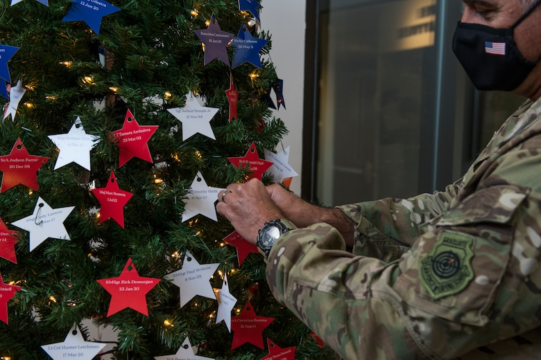 U.S. Air Force Maj. Gen. Eric Hill, deputy commander of Air Force Special Operations Command, places stars on an Honor Tree.
