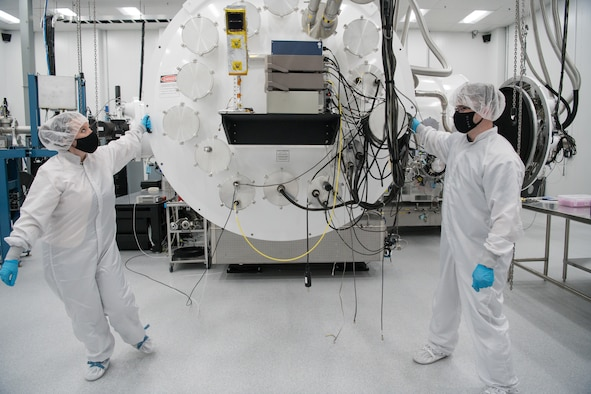 Kellye Burns, left, a space test engineer, and Eric D'Ambro, a test operations engineer, open the door of a Space Asset Resilience thermal vacuum chamber, Aug. 3, 2020, at Arnold Air Force Base, Tenn. The chamber is contained in a class 10,000 clean room. (U.S. Air Force photo by Jill Pickett)