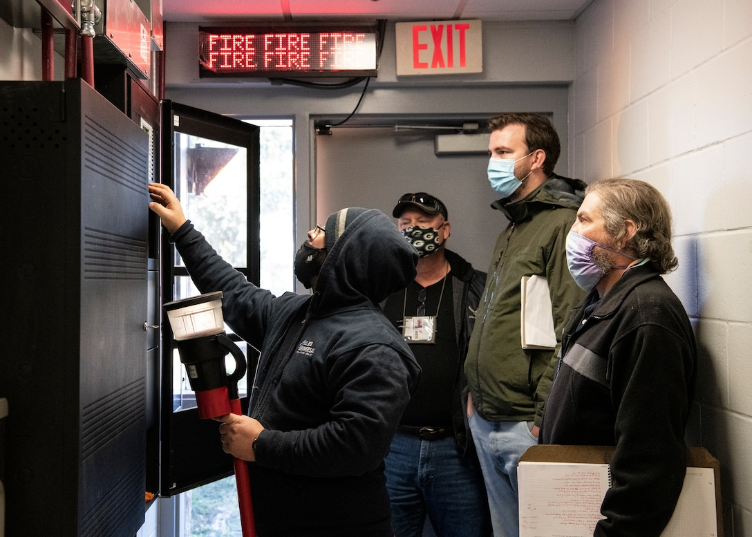 Photo of four people looking at a fire suppression panel