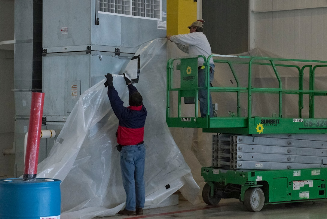 Photo of two workers putting plastic sheets against a wall