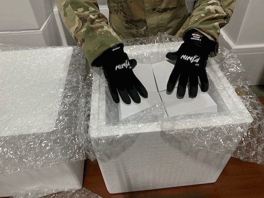 An Ohio National Guard member wears special gloves while practicing to pack glass vials in dry ice in preparation for when Ohio begins receiving the COVID-19 vaccine. About two dozen Ohio National Guard members have been working with the Ohio Department of Health to develop the logistics plan to receive and repackage the vaccine for distribution.