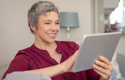 Smiling senior woman looking her digital tablet while sitting on sofa. Portrait of mature happy woman relaxing at home with digital tablet. Happy lady with gray hair browsing on laptop in living room.