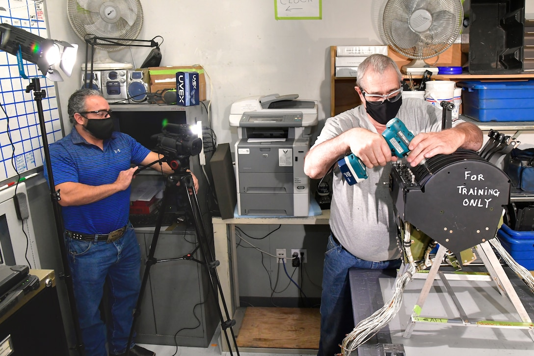 (Left to right) Scott Stokes, OO-ALC/OBH, Training office, films Trent Mikesell, C-130 Aircraft Mechanic, 309th AMXG, demonstrating work on an engine control quadrant during the making of a training video, Dec. 7, 2020, Hill Air Force Base, Utah.