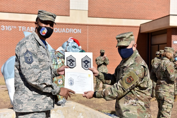 U.S. Air Force Col. Andres Nazario, 17th Training Wing commander, presents Chief Master Sgt. select Aaron Shirley, 316th Training Squadron superintendent, with stripes and a certificate with his line number at the 316th TRS on Goodfellow Air Force Base, Texas, Dec. 4, 2020. Chief master sergeants serve as key leaders at all levels in the Air Force. (U.S. Air Force photo by Staff Sgt. Seraiah Wolf)
