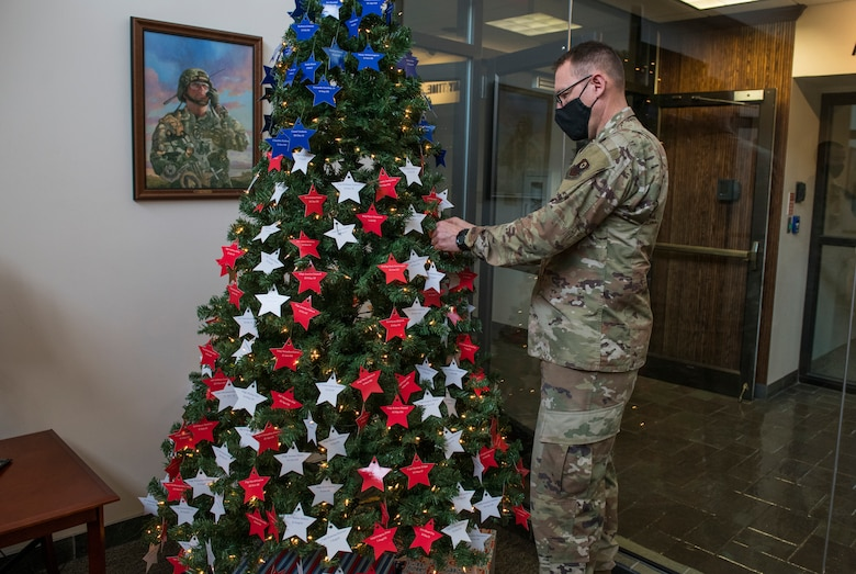 U.S. Air Force Chief Master Sgt. John Lang, superintendent of the 1st Special Operations Maintenance Group, places stars on an Honor Tree.
