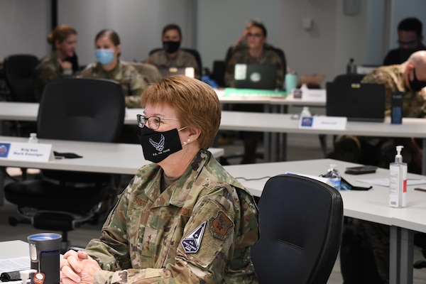 Image of an Airman sitting at a table wearing a mask.