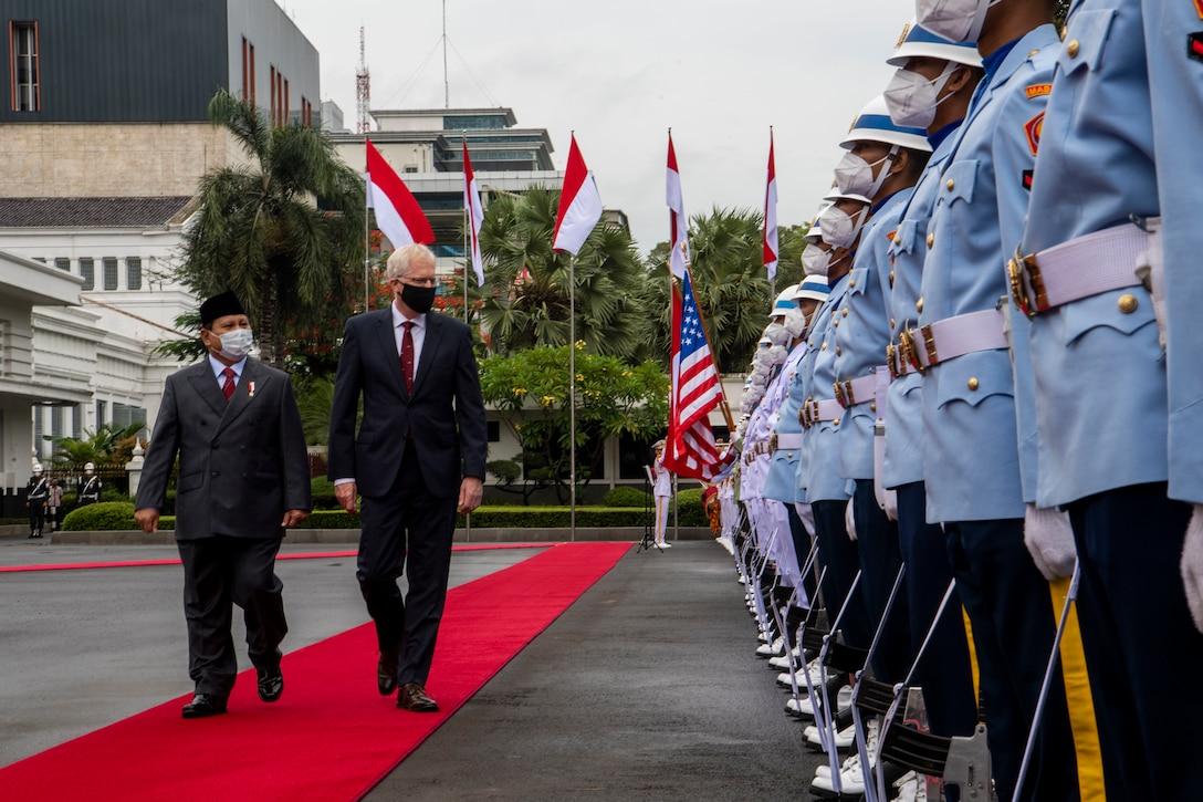 Two men walk by a row of men in uniform.
