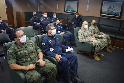 Military personnel listen to a briefing.