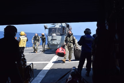 Military personnel board a ship.