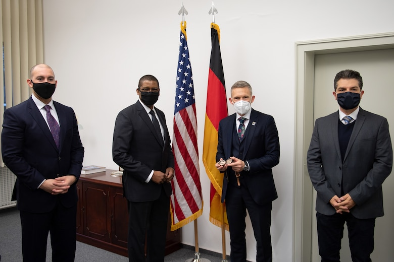 Four men standing around the American and German flags.