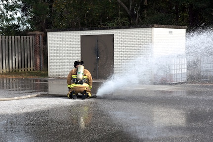 Chaz Cools, a firefighter for the 628th Civil Engineer Squadron, demonstrates how to stop a faulty hose from losing control by diving and applying pressure on the hose, at Joint Base Charleston, S.C., Dec. 3, 2020. Swift and his team members at the 628th CES Fire Department support the mission by saving lives and protecting the people of Joint Base Charleston.