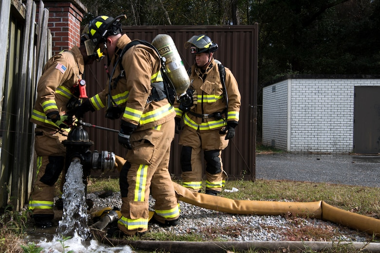 Civilians and Airmen from the 628th Civil Engineer Squadron, dismount a faulty hose from a fire hydrant during a training exercise, at Joint Base Charleston, S.C., Dec. 3, 2020. Swift and his team members at the 628th CES Fire Department support the mission by saving lives and protecting the people of Joint Base Charleston.