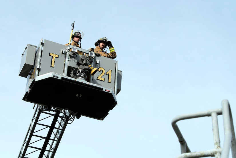 Danny Drake (left) and Chaz Cools (right), firefighters from the 628th Civil Engineer Squadron, navigate controls from the bucket and begin to position themselves for access to the roof of the training building, at Joint Base Charleston, S.C., Dec. 3, 2020. Swift and his team members at the 628th CES Fire Department support the mission by saving lives and protecting the people of Joint Base Charleston.