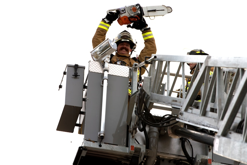 Chaz Cools, a firefighter from the 628th Civil Engineer Squadron, wields a chainsaw and poses for a picture, at Joint Base Charleston, S.C., Dec. 3, 2020. Swift and his team members at the 628th CES Fire Department support the mission by saving lives and protecting the people of Joint Base Charleston.
