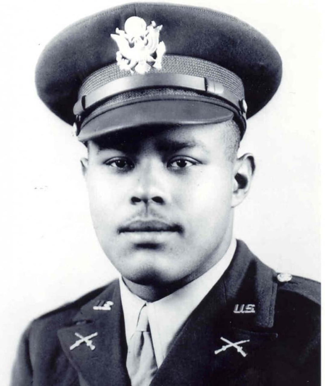A man in an officer's uniform looks at the camera.