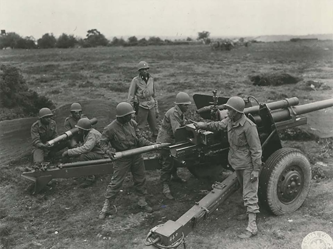 Seven men stand around a field artillery station.