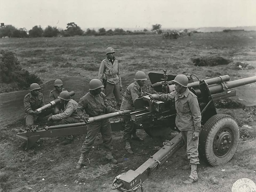 Seven men stand around a field artillery station.
