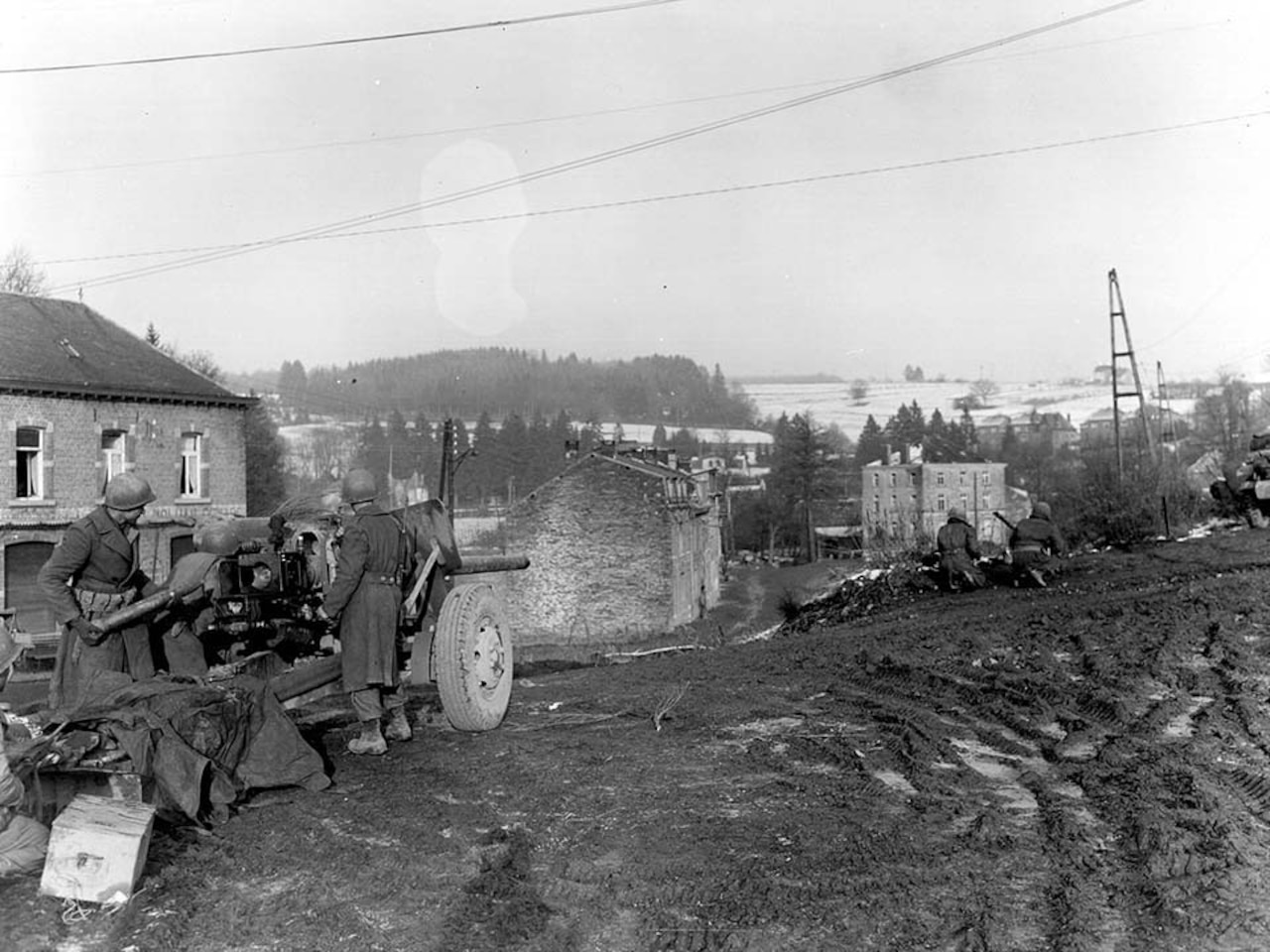 Two men prepare a field artillery gun while two more men crouch down looking in the distance at a town.