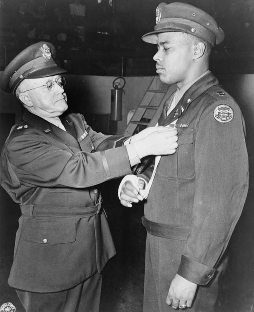 A man in an officer's uniform pins a medal to the lapel of the uniform worn by a man whose arm is in a sling.