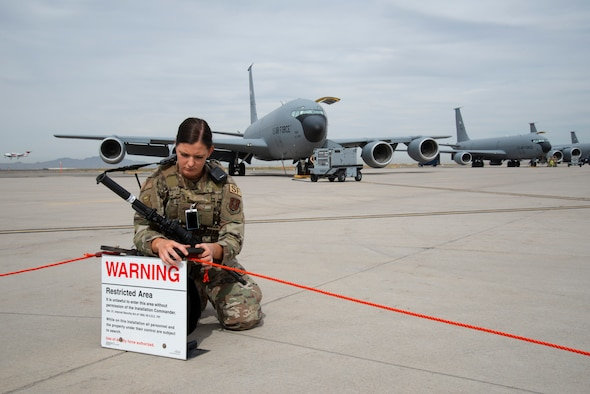 A female Security Forces Airman in Air Force uniform, kneels on a flightline while stretching a red cord out with a KC-135 Stratotanker behind her.
