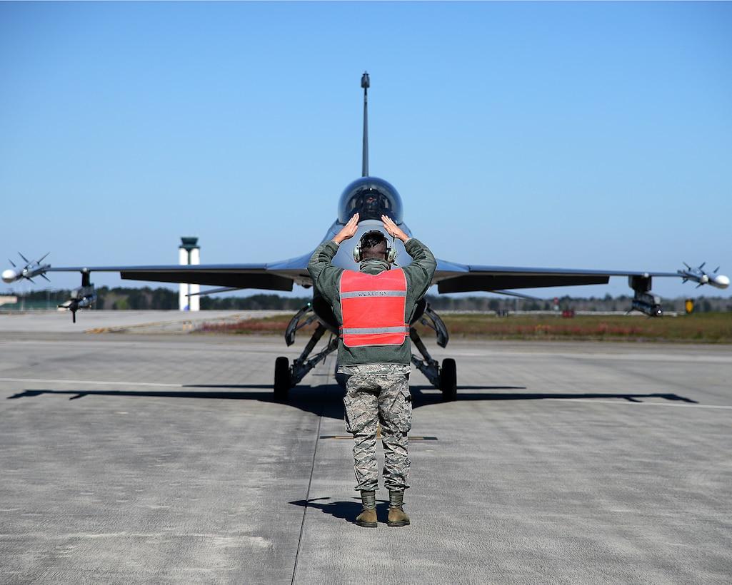 A photo of Tech. Sgt. Jeffrey J. Rain signaling an F-16 Fighting Falcon prior to launch.