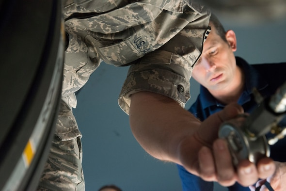 An Airman's hand enters the frame, holding an instrument to measure pressure.
